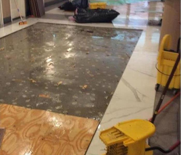plywood on flooded surface in a lobby