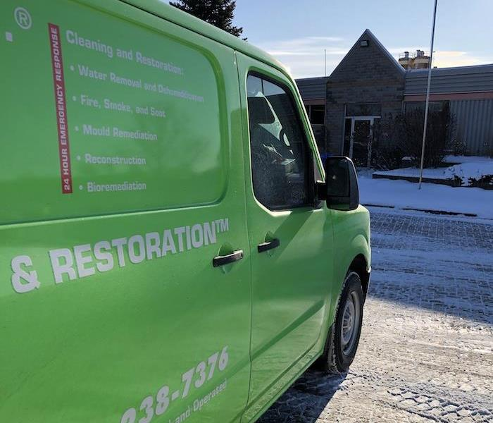 SERVPRO green service van parked outside jobsite