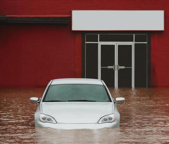 A red building with a car and standing water in the parking lot.